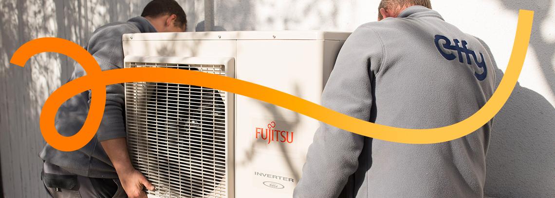 Deux hommes installant un module externe de pompe à chaleur