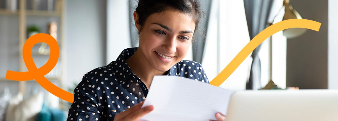 Femme qui regarde un document en souriant