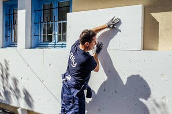 Artisan Effy pose un isolant en panneau sur murs extérieurs