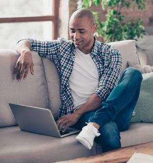 Homme sur un canapé avec un ordinateur