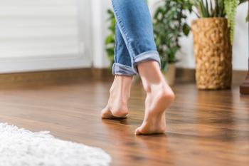 Une femme marche pied nus sur son plancher